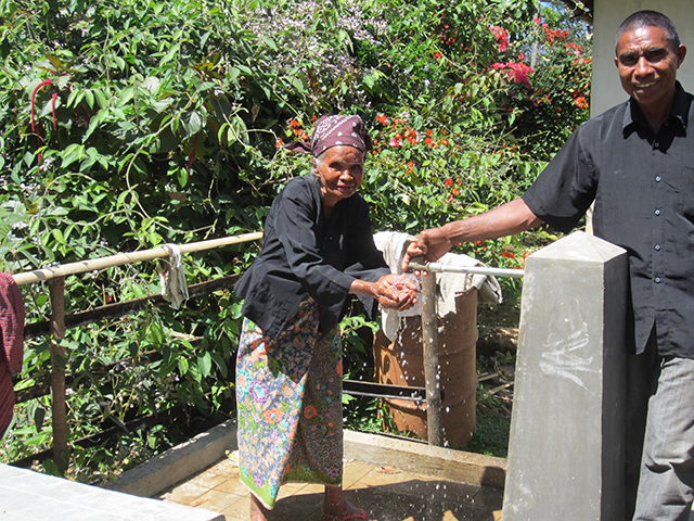 Women in developing country using running water infrastructure sponsored by WaterAid